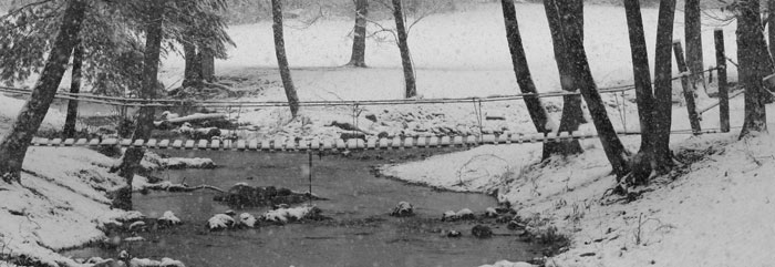 creek in snow with foot bridge